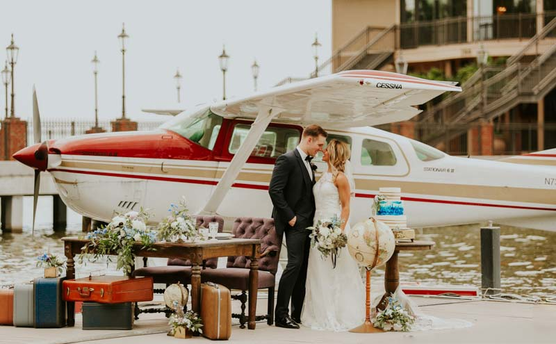 couple standing on dock next to a seaplane for lakeside wedding inspiration