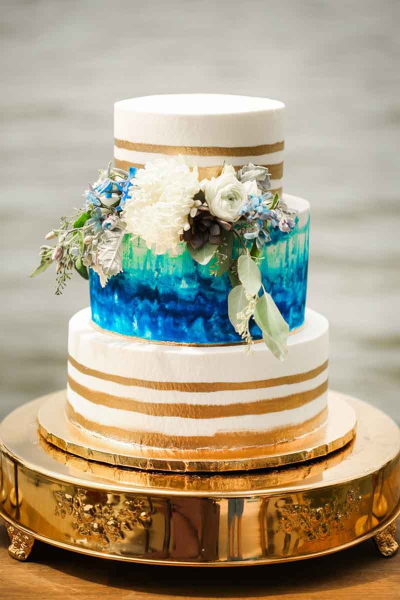 gold and blue watercolor wedding cake on gold cakestand