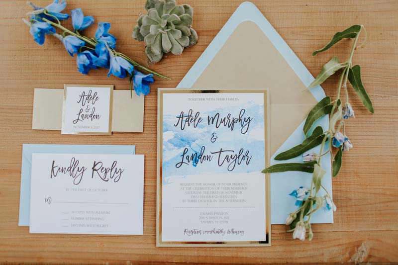 watercolor blue and gold invitation suite with flowers around it