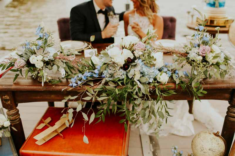 greenery centerpiece with blue and purple flowers on farm table