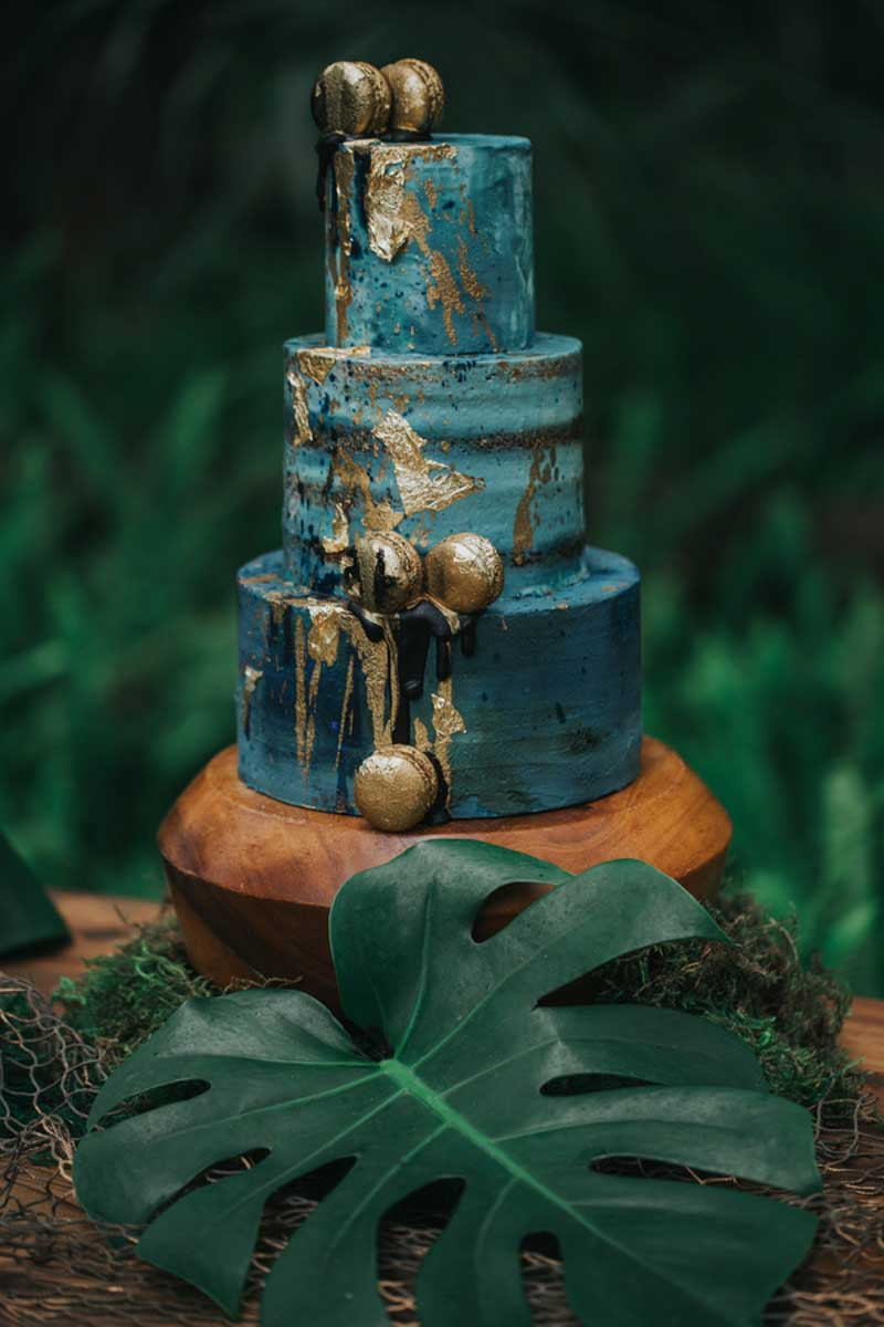 teal colored wedding cake with gold foiled macrons