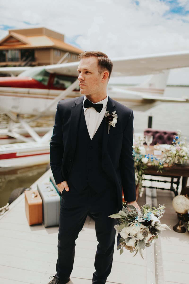 groom standing on dock in front of seaplane