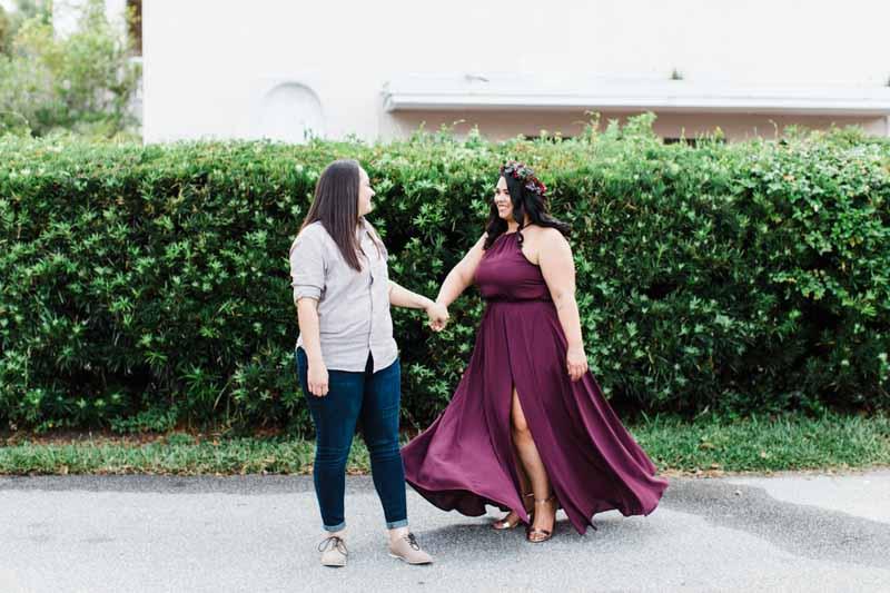 woman twirl in burgundy dress holding partner's hand