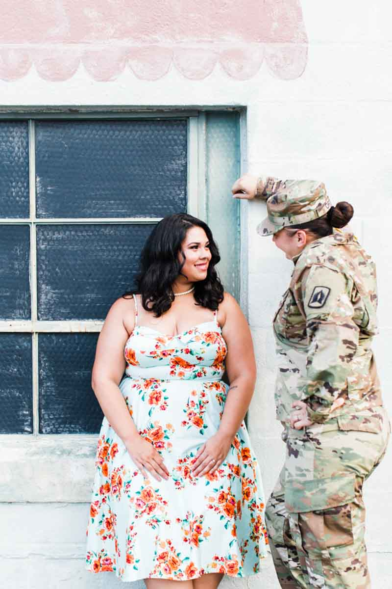 woman leaning on wall looking at fiance