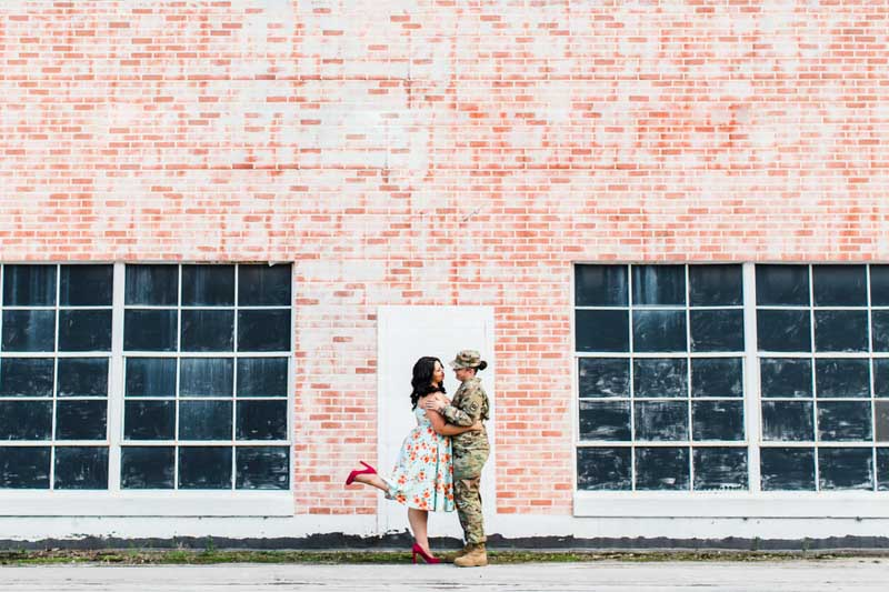 women standing in front of brick wall for engagement session