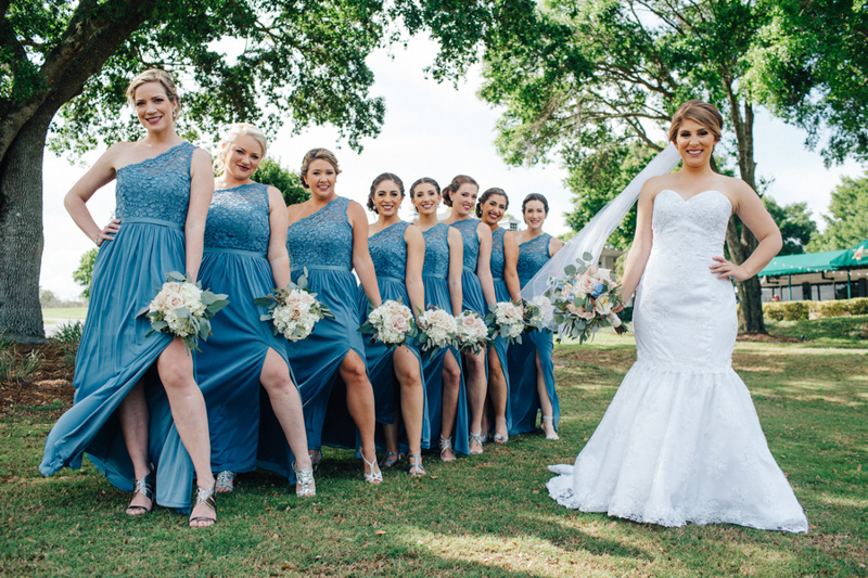 bridesmaids in blue dresses holding bouquets