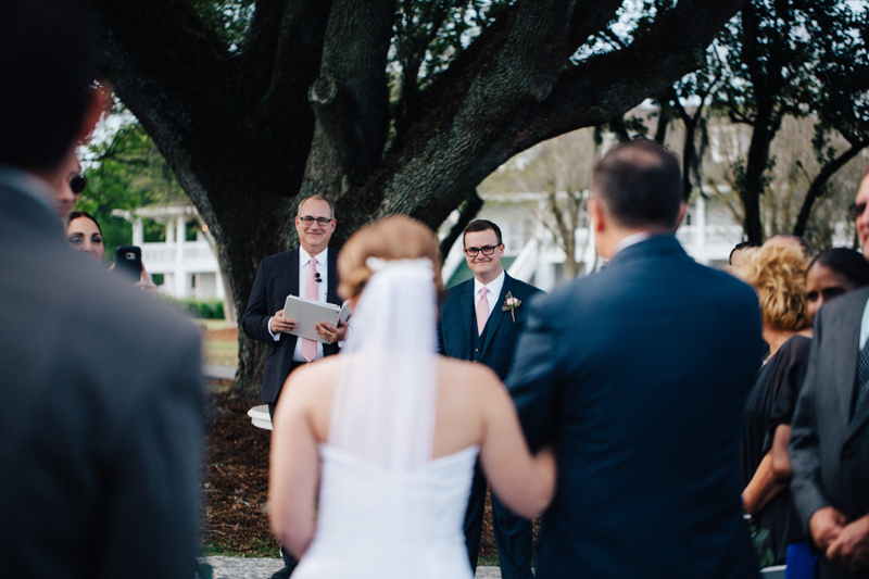groom smiling at bride walking up the aisle