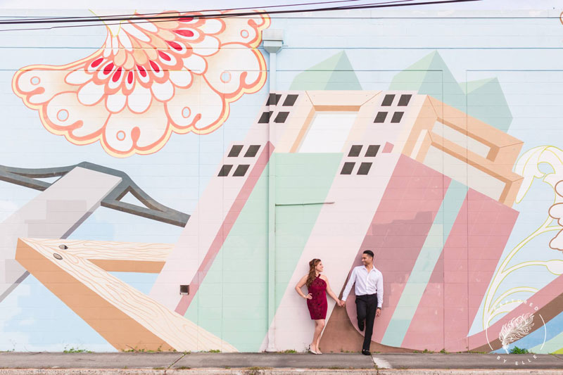engaged couple leaning on wall mural in Mill 50 Orlando