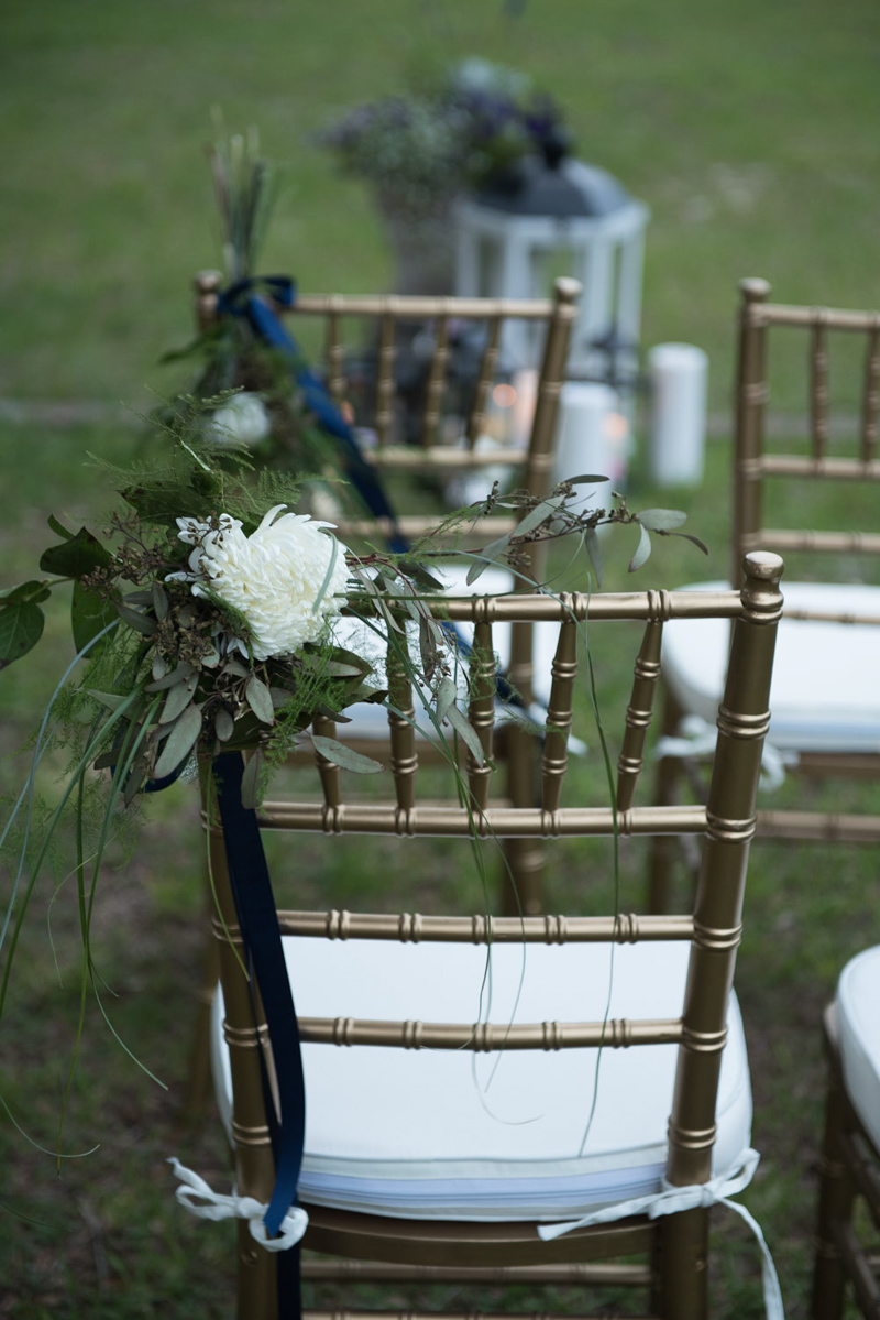 floral wedding ceremony pieces on gold chiavari chairs