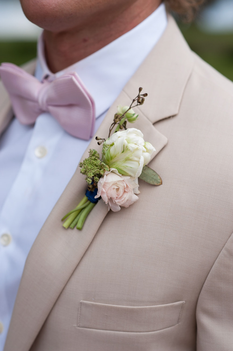 white and blush boutonniere on tan coat